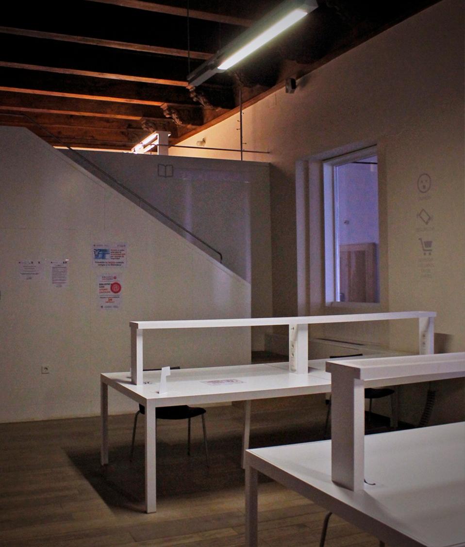 Imagen en la que se puede observar varias mesas y sillas de una sala de escritorio