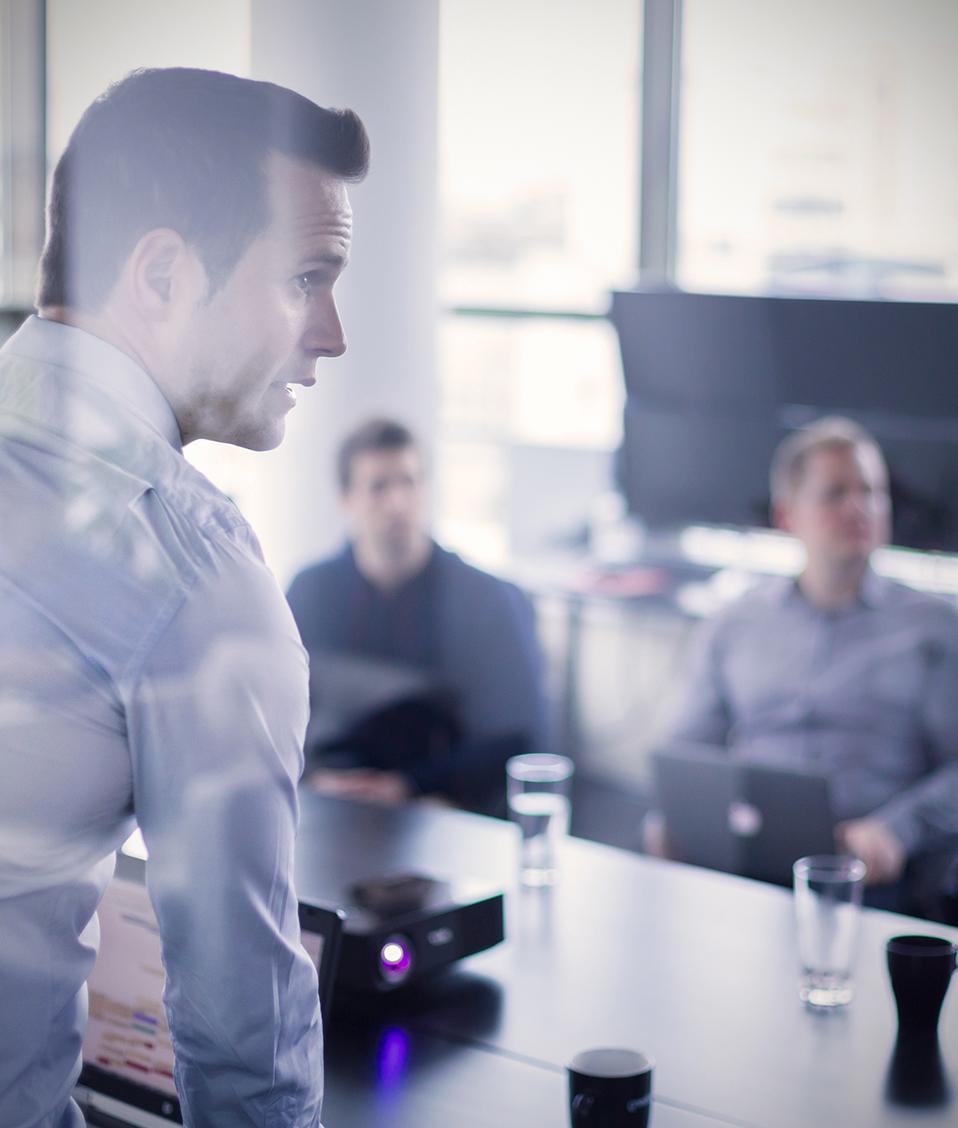 Grupo de personas en una sala de reuniones mientras una de ellas expone con el uso de un proyector