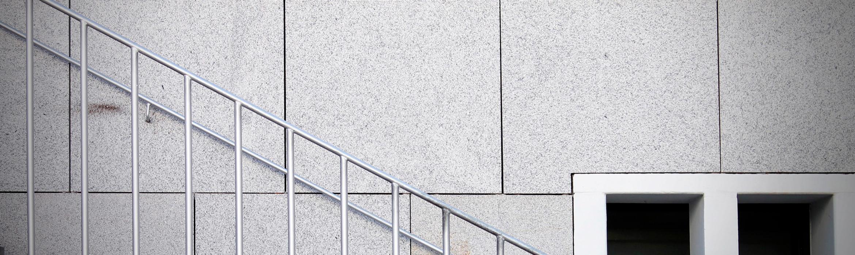 Imagen en la que se muestra el detalle de una barandilla metálica de unas escaleras, a la derecha hay un par de ventanas