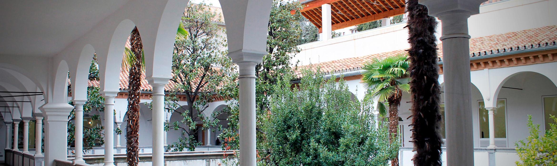 Imagen en la que se puede observar varias columnas agrupadas formando arcos, en el fondo de la imagen se puede observar un jardín