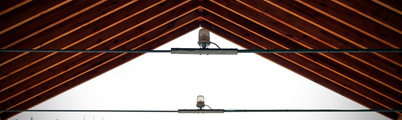 Detalle de una bombila situada en una sala exterior con un tejado de madera